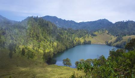 crater highlands: landscape with mountains trees and a lake at Ranu Kumbolo, Semeru Volcano Mountain, East Java, Indonesia. Semeru Mountain also known as Mahameru Mountain in Indonesia means the great mountain. Foto de archivo