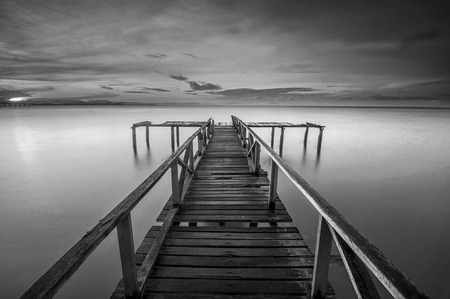 long lake: Calm scene in black and white with abandoned jetty at Teluk Tempoyak, Penang, Malaysia. black and white fine art Stock Photo