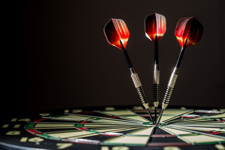 Red, black, and green dartboard on its side with three fiery metal tipped darts in the bulls eye. On black background. Stock Photo
