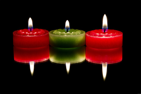 Three candles, reflected, on dark background photo