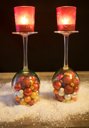 filled roll: Christmas wine glasses with Christmas balls and candle in the snow