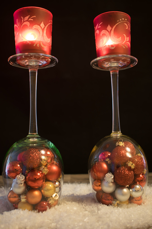 upturned: Christmas, wine glasses with Christmas balls and tea light in the snow