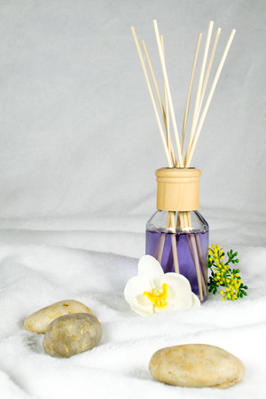 A decorative bottle with purple fragrance oil, along with flowers and stones on a fluffy background