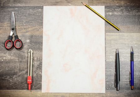 On a subsoil of wood are clear arranged a patterned sheet of paper, 2 ballpoint pens, a pencil, a circle and scissors