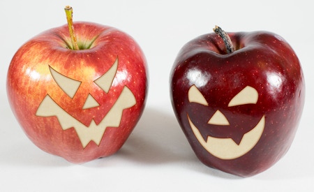 2 red apples with funny carved faces on a white background Stock Photo