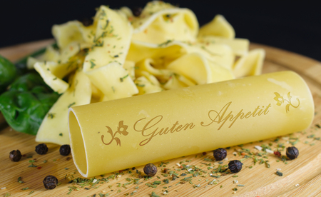On a wooden board is in the foreground a cannelloni with the lettering - bon appetite - in german words, in the background are further noodles garnished with leaf spinach and pepper grains Archivio Fotografico