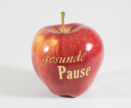 1 fresh red apple with the words - Healthy break - in german language