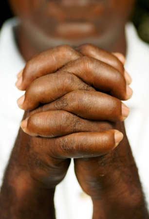 interlocked: fingers of afro man clasped in front of his body