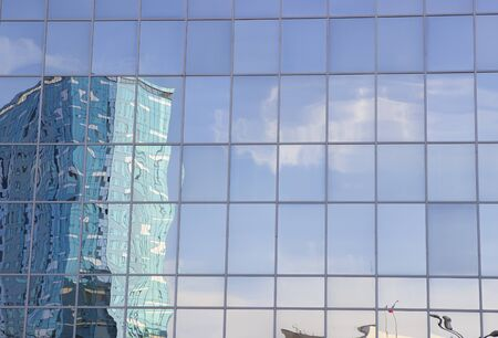 Looking up the facade of an office building, as a reflection of a large mirror the facade of the building.