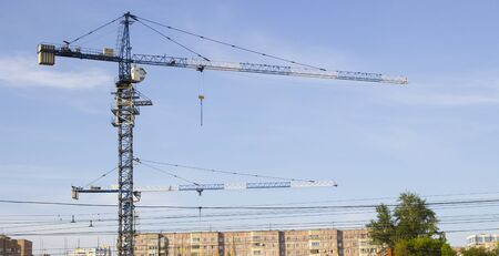 Working crane in the sky. Construction site. Construction of a large house