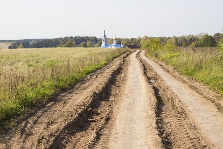 Road on a grass covered land with church steeple and rooftop background. Russian field.