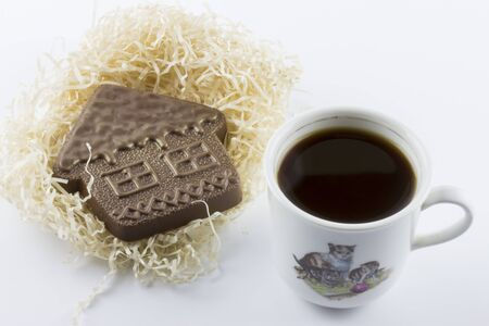 Chocolate house and a Cup of coffee. Figures made of chocolate, Delicious dessert. Confectionery A restaurant 写真素材