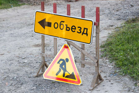 Works ahead warning sign on a road. Road sign road repairs and the sign of the Detour translated from the Russian language 写真素材