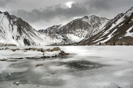 frozen lake: Winter scenery. Frozen lake surrounded by a mountain range in a dark stormy weather. Stock Photo