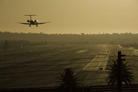 Small jet is about to land on runway. Sunset light gives a gold cast to the entire image. San Diego Airport, California,USA.