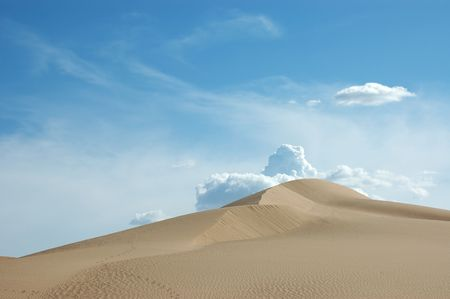 Sand dune in the desert. A smooth sand dune against blue sky. Storm is forming behind it. Imperial County, near El Centro in southern California. Stock fotó