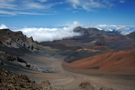 The crater of a volcano.Red dirt rocks and a blue sky form this amazing moon like landscape of this volcano top, above the clouds. Haleakala National Park in Maui, Hawaii.
