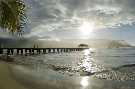 People walking at the pier and watching the beauty of a tropical paradise. Sun reflecting on the sea with the silhouette of the dock surrounded by the mountains and one palm leaf.Hanalei Bay,Kauai. Hawaii Islands.