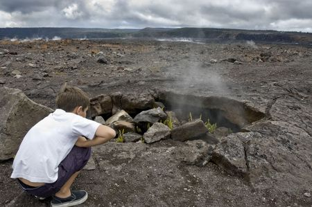 A curious boy is studying a lava hole where some fern plant is just sprouting and steam is coming out of it. Hawaii Volcanic Park. Big Island.