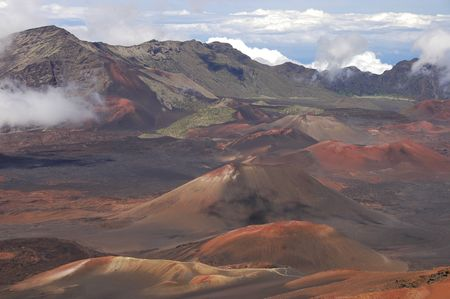vulcanology: The crater of a volcano.Red dirt rocks and a blue sky form this amazing moon like landscape of this volcano top, above the clouds. Haleakala National Park in Maui, Hawaii.