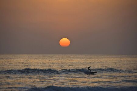 Surfer riding a wave and sun setting behing him.