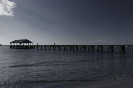 Hanalei pier in Kauai.People walking at the harbor in the afternoon.