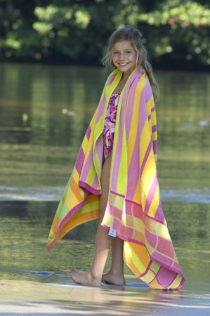 Little girl smiling at camera, surrounded by lush green nature, wrapped in a colorful towel.