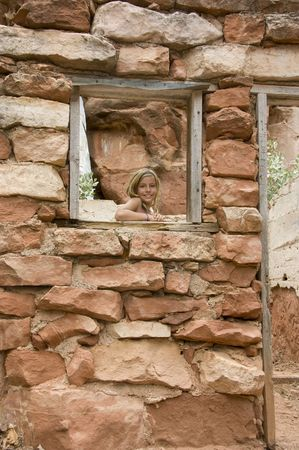 Kid posing by a window frame at a house made of red rocks in Sedona, Arizona. She is smiling and looking at the camera. She is about 9 years old. Stock Photo
