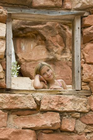 Kid posing by a window frame at a house made of red rocks in Sedona, Arizona. She is smiling and looking at the camera. She is about 9 years old. Stock fotó