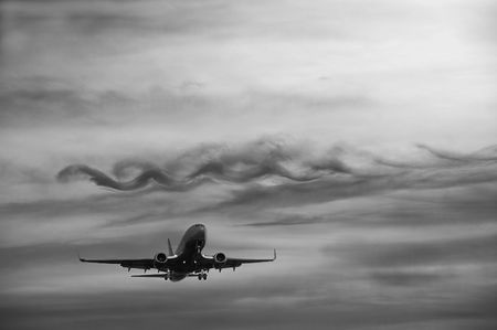 Airplane flying in the sky, dramatic clouds. Black and White. Copy-Space.