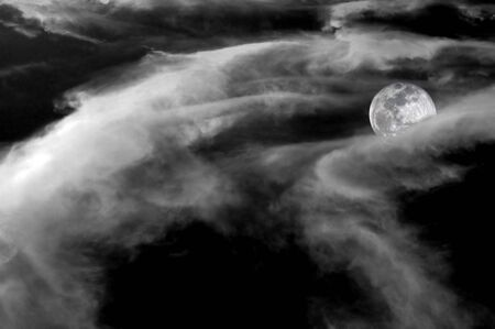 Spooky full moon half covered in contrasting clouds. Black and White.  Stock fotó