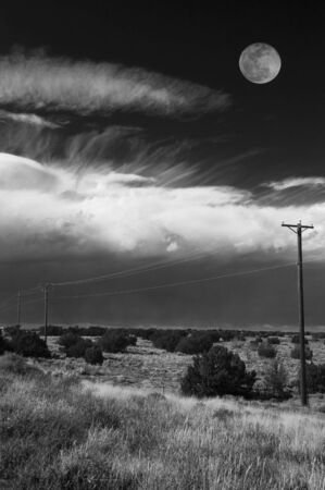 Full Moon over bright dramatic clouds and power lines. Black and White. Horizontal.