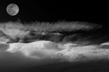 Full moon shining over a thick cloud with a n electricity pole on the bottom. Black and White.