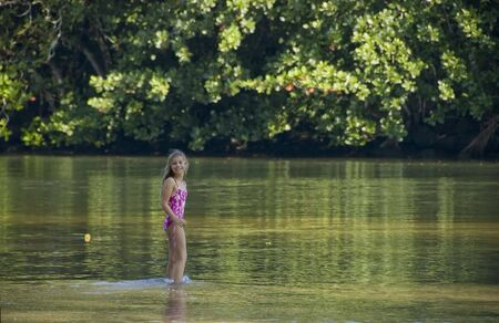 Young girl in pink swimsuit, playing in the green river, looking at camera and surrounded by tropical forest.