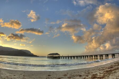 Wide angle view of Pier at Hanalei Bay  Beach in Kauai during sunset. HDR.