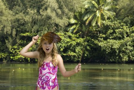 Young girl in pink swimsuit, playing in the jungle, looking at camera and surrounded by green river in a tropical forest.