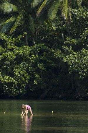 Little girl playing in the green river in a tropical green forest.