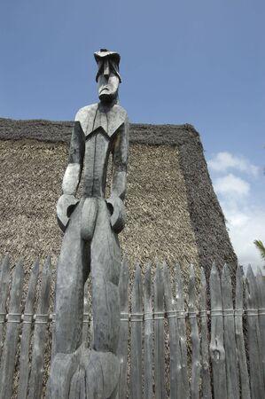 Naked Tiki idol with a sad face. Primitive polynesian carving.Tall wood carved  male human figure against wood fence and local hut. Big Island of Hawaii. Puuhonua O Honaunau, National Historical Park. Place of Refuge.