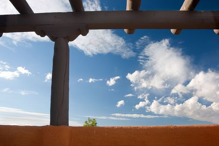 Southwestern architecture. Beams and earth colored wall against blue sky, one little tree showing up behind the wall. New Mexico