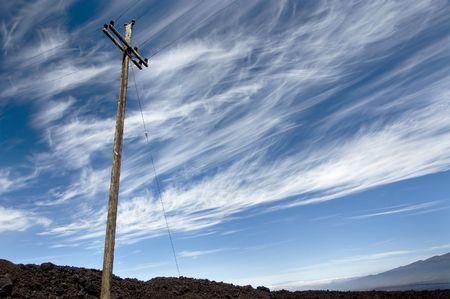 Power line on volcanic rocks against dramatic sky. Big Island of Hawaii.