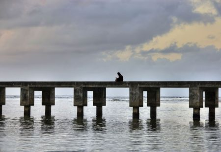 Woman reading book while seated on top of the pier during sunset at the beach.