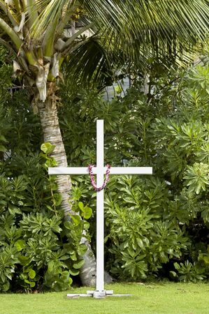 Big white cross or crucifix surrounded by tropical plants , palm tree and one flower lei hanging on it. Aloha Spirit. Stock Photo