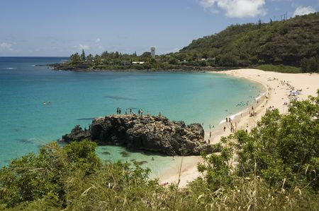 Crystal clear water and big lava rock in a sunny day at the Waimea Bay. North Shore of Oahu. Hawaii.