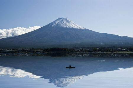crater highlands: Monte Fuji en un d�a claro, su reflexi�n sobre el lago y el pescador en un barco. Kawaguchi, Jap�n  Foto de archivo
