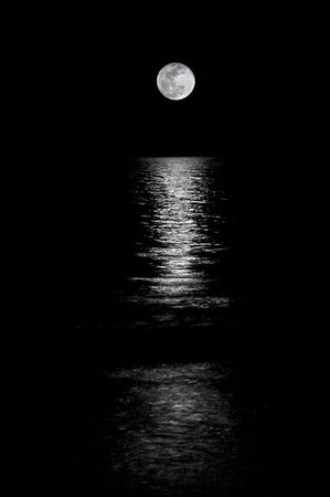 Full moon setting on the horizon in the ocean with reflection shining thru. Black and White. Stock Photo