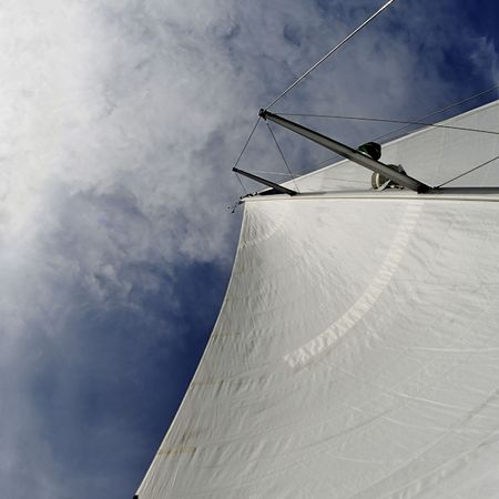 Sail from sailboat against blue sky, sun and clouds. Square format, wide angle. Stock Photo