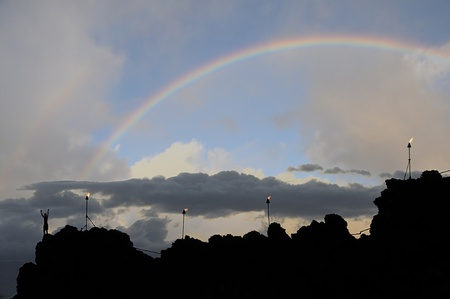 Rainbow over black lava rocks and torches. Maui.