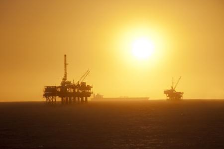 pozo petrolero: Plataformas de petróleo en el océano, barco pasando por y un hermoso atardecer en Huntington Beach, California.