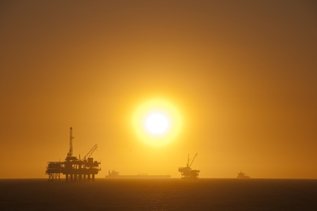 well platform: Oil rigs, ship and sunset in the ocean. Huntington Beach, California.