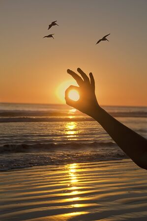 Sunset at the beach and child is covering the sun with  Ok hand sing. Birds flying around. Southern California on 101010. Stock Photo